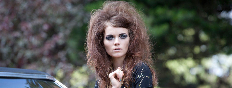 Donna con capelli cotonati e trucco con eyeliner molto deciso in piedi davanti a un'automobile