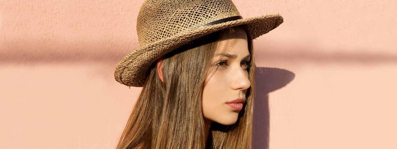 Donna di profilo con capelli castano chiaro lisci e cappello