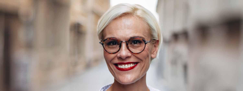 Donna sorridente con capelli bianchi, occhiali e taglio pixie