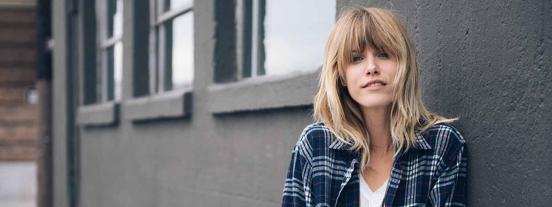 Blonde Frau mit kariertem Hemd steht an eine Hauswand gelehnt