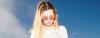 Mädchen mit blonden, mittig gescheitelten Haaren im Undone-Look trägt eine rote Sonnenbrille und schaut auf ihr Handy