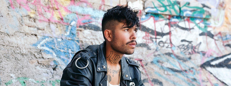 Tätowierter Mann mit schwarzem Haar und Lederjacke trägt eine Rockabilly-Frisur