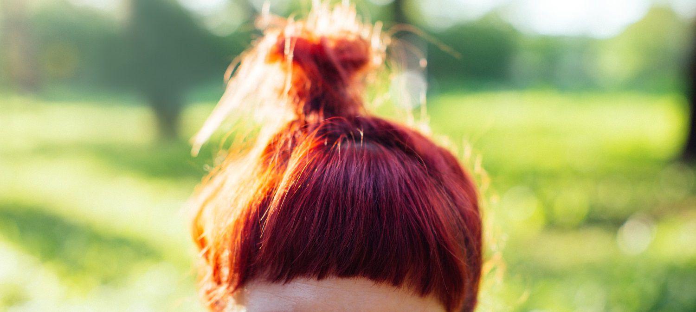 Donna con capelli rossi, chignon e frangetta netta a metà fronte