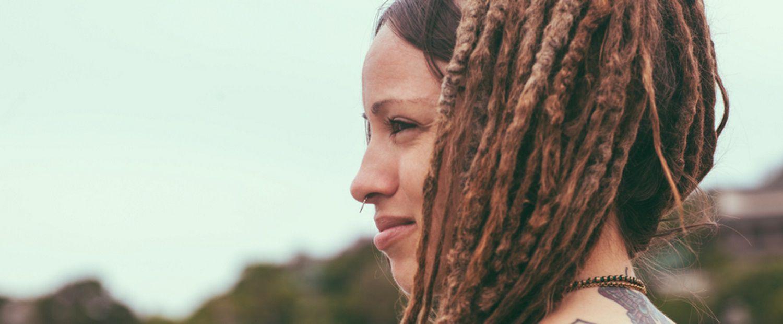 Donna con dreadlocks e tatuaggi fotografata di profilo