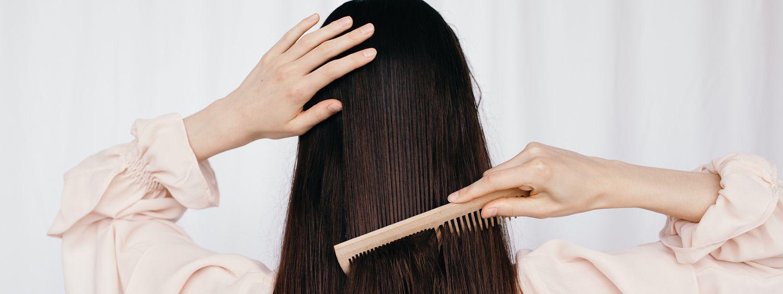 Femme vue de dos en train de peigner ses longs cheveux bruns
