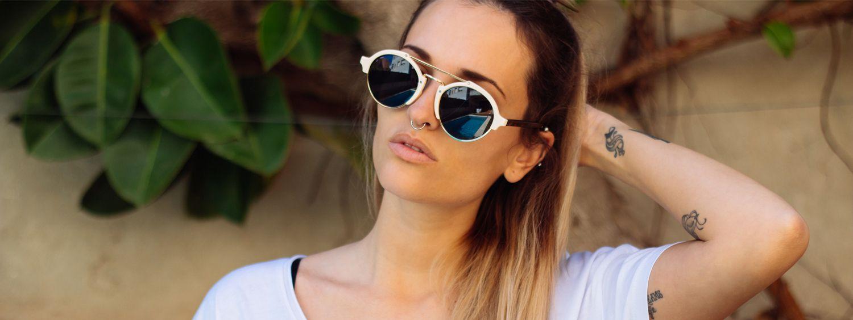 Frau mit langen Haaren im Balayage-Look trägt weißes T-Shirt und Sonnenbrille