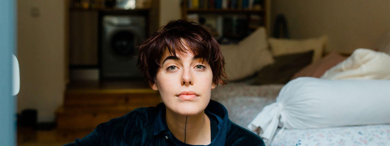 Femme brune aux yeux bleus en train de poser chez elle, assise sur le sol