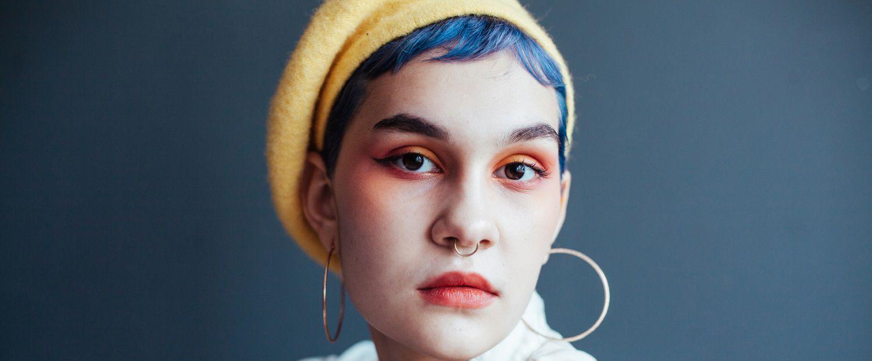 Donna con capelli azzurri e taglio pixie, con un cappello giallo e orecchini grandi ad anello