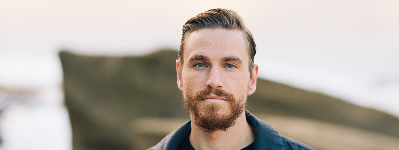 Blonder Mann mit Bart schaut frontal in die Kamera
