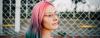 Junge Frau vor einem Zaun mit Brille und bunten Haaren