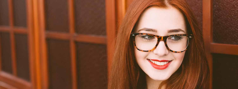Donna con lunghi capelli rossi, riga in mezzo, rossetto rosso e occhiali che sorride