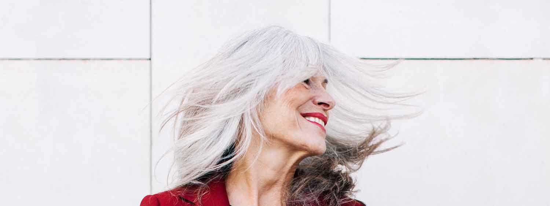 Uśmiechnięta kobieta o siwych włosach