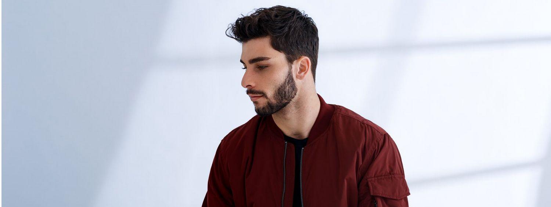 Homme avec une barbe et des cheveux bruns portant une veste rouge foncé.