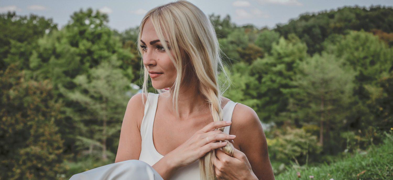 Femme blond portant une robe blanche en train de se tresser les cheveux