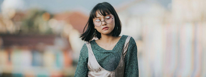 Femme avec des lunettes rondes et un carré frangé en train de marcher dans la rue