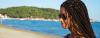 Portrait einer dunkelhaarigen Frau mit Braids und Sonnenbrille am Strand