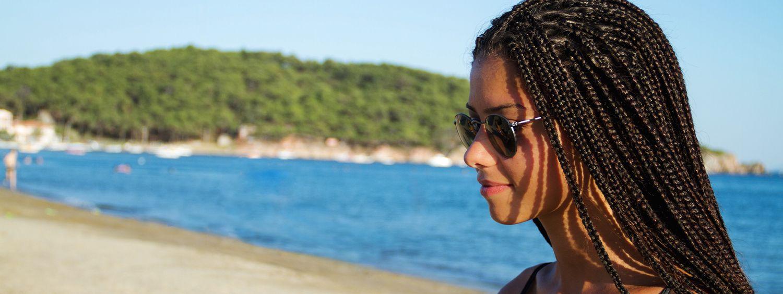 Donna di profilo con occhiali da sole e capelli afro intrecciati