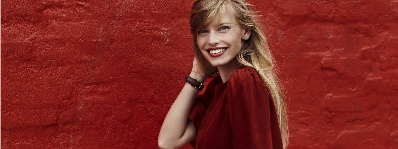 Jeune femme blonde avec frange longue en train de sourire