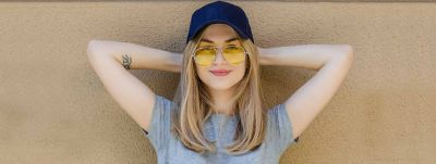 Blonde woman with straight hair and blue baseball cap