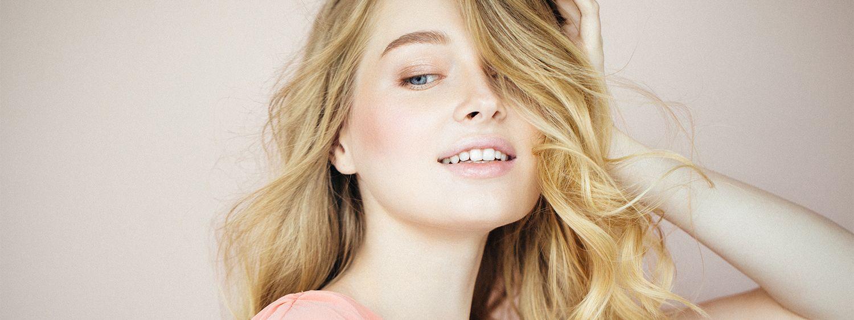 Lächelnde blonde Frau mit langen Locken fasst sich in die Haare.