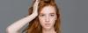 Rothaarige Frau mit langem, welligem Haar fässt sich in die Haare