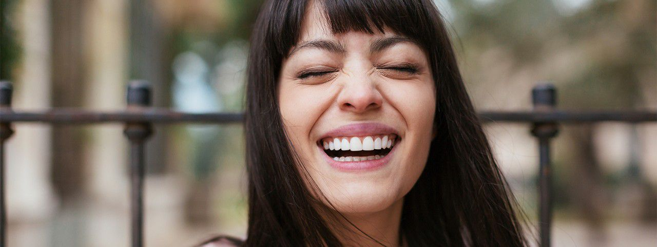Dark-haired woman with long hair and bangs, laughing.