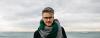 Grauhaariger Mann mit Schal am Strand
