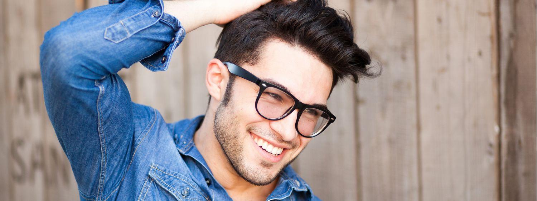 Homme brun avec des lunettes noires et une coupe dégradée