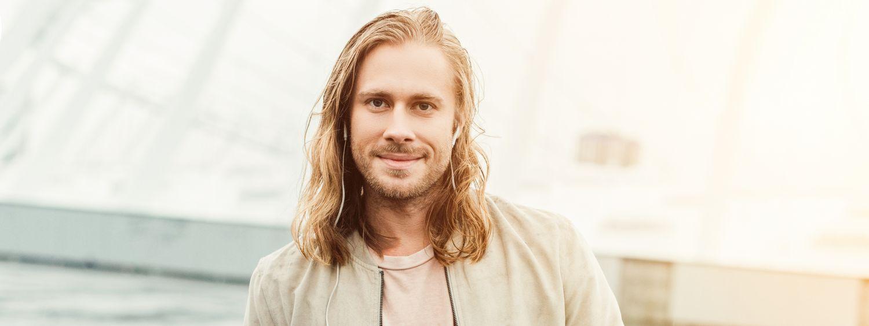 Homme aux longs cheveux blonds en train d'écouter de la musique