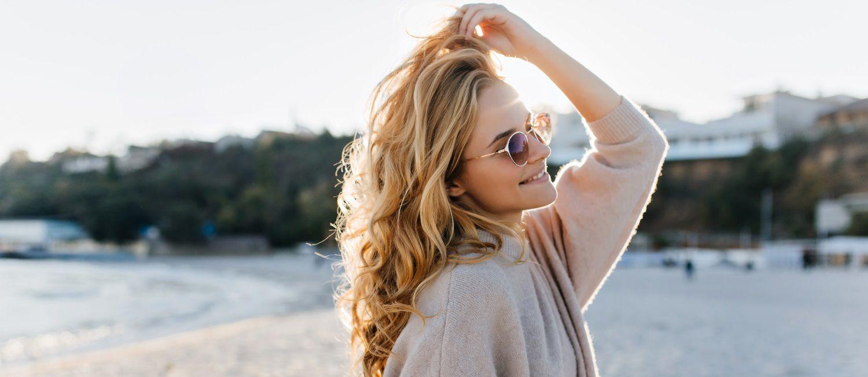 Femme blonde sur une plage avec un cardigan taupe et des lunettes de soleil