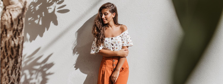 Jeune femme brune adossée à un mur blanc