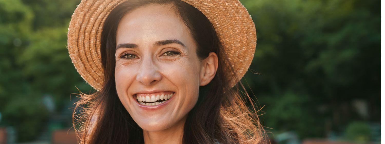 Femme brune avec un chapeau de paille en train de sourire