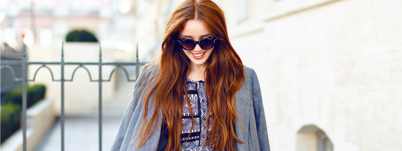 Jeune femme rousse avec lunettes de soleil se promenant dans la rue