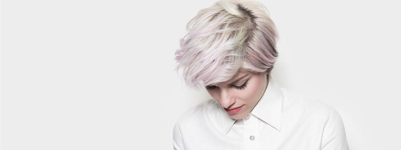 Femme aux cheveux courts blancs avec reflets rose devant un mur blanc