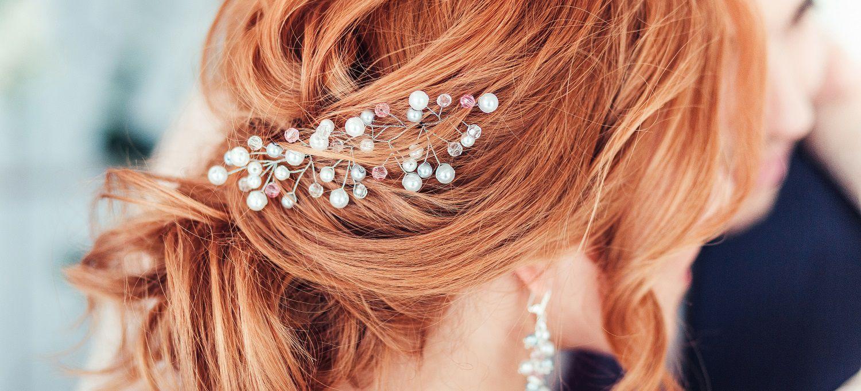 Gros plan sur une coiffure de mariée avec boucles et barrettes en strass