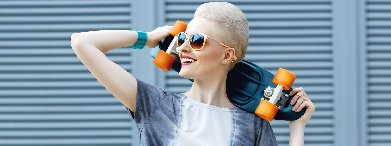Femme blonde aux cheveux courts avec des lunettes de soleil tenant un skateboard