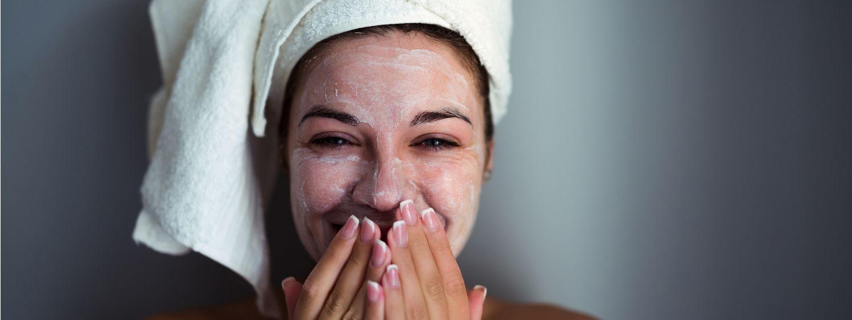 Femme en train de rire avec un masque visage et une serviette sur les cheveux