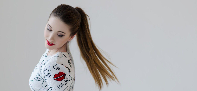 Profil de jeune femme avec une queue-de-cheval haute et du rouge à lèvres