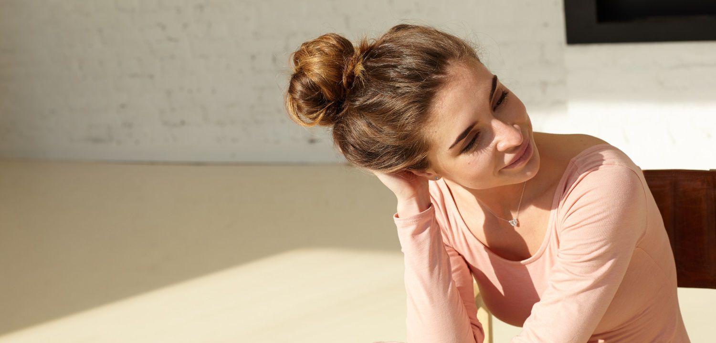 Jeune femme brune au soleil en train de retoucher son chignon haut