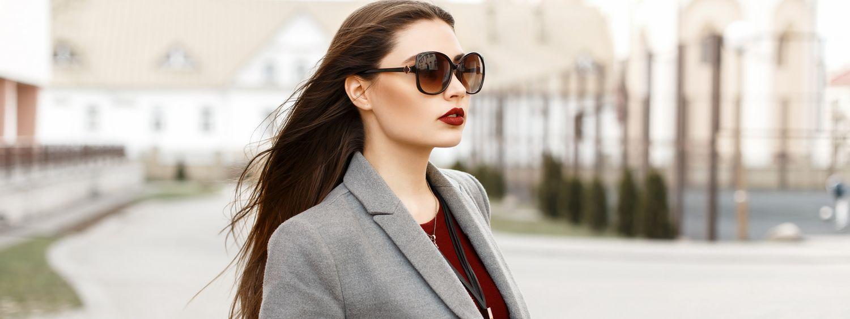 Femme brune avec lunettes de soleil en train de marcher dans la rue