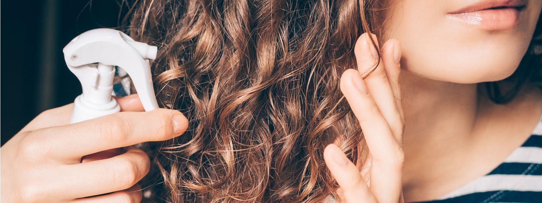 Femme vaporisant du vinaigre de cidre sur ses cheveux châtains