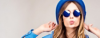 Beautiful young woman with shorter brown hair sending kisses in blue glasses and hat