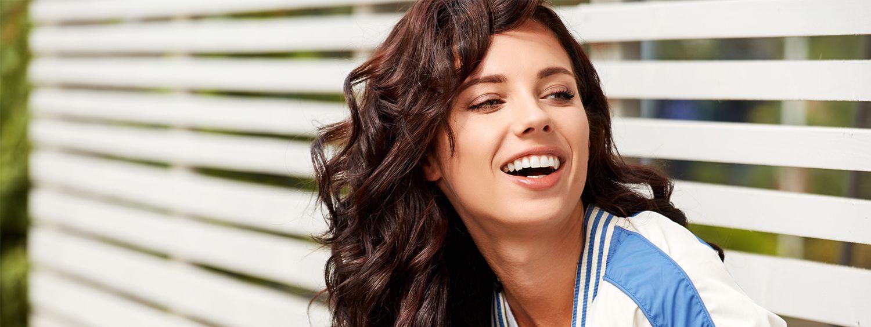 Braunhaarige Frau mit großen, langen Locken in blau-weißer Jacke blickt lachend am Fotografen vorbei