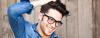 Dunkelhaariger Mann mit dunkler Brille hat die Haare zu einem Sidecut gestylt