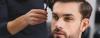 Brünetter Mann mit Dreitagebart und Kurzhaarschnitt betrachtet seine Geheimratsecken