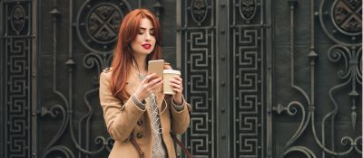 Woman with dyed red hair holding cell phone and coffee cup