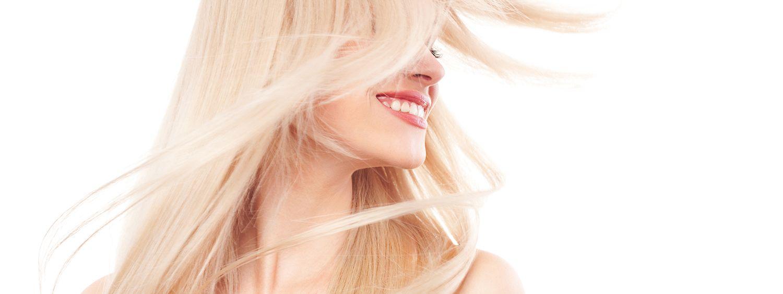 Blonde Frau schwingt ihre langen Haare