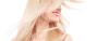 Lächelnde Frau mit weißem Oberteil schüttelt ihre langen, blonden Haare