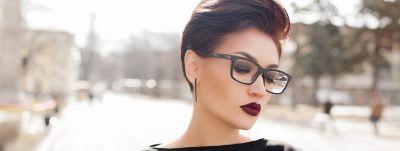 Dunkelhaarige Frau mit Brille und dunklem Lippenstift trägt ihre längeren Haare zu einer Kurzhaarfrisur nach hinten gestylt