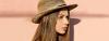 Seitliche Nahaufnahme einer braunhaarigen Frau mit geglätteten Haaren und Strohhut